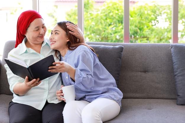 Een oudere vrouw met kanker die een hoofddoek draagt, ontspant thuis met haar volwassen dochter en leest lachend een boek. de vrouwen zijn vol hoop voor de toekomst.