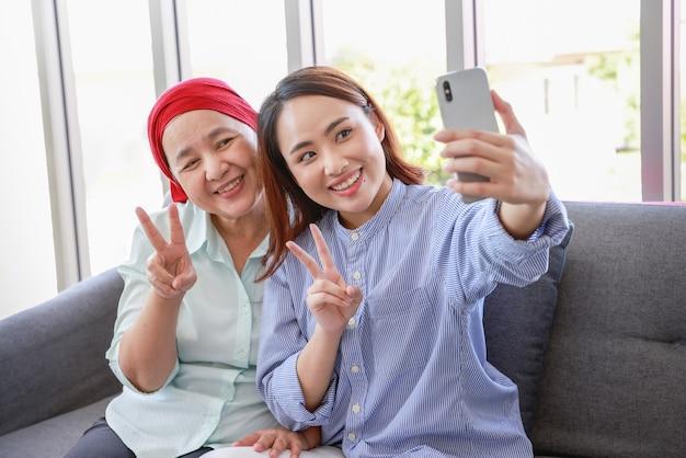 Een oudere vrouw met kanker die een hoofddoek draagt, ontspant thuis met haar volwassen dochter en maakt een foto met de smartphone in de woonkamer. de vrouwen zijn vol hoop voor de toekomst.