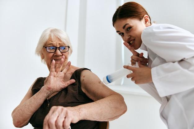Een oudere vrouw op een doktersafspraak een grote spuit immuniteitsbescherming