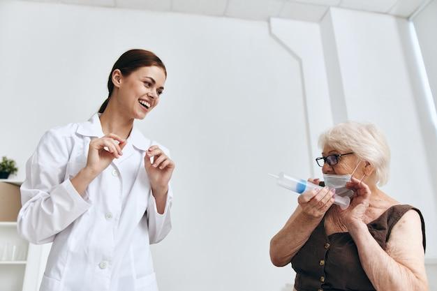 Een oudere vrouw op een doktersafspraak een injectie in de arm immuniteitsbescherming
