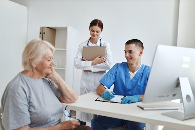 Een oudere vrouw op een doktersafspraak en een communicatiebehandeling van een assistent-zuster