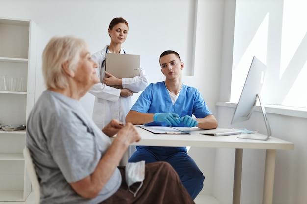 Een oudere vrouw op een doktersafspraak en een verpleegster in een ziekenhuiskantoor