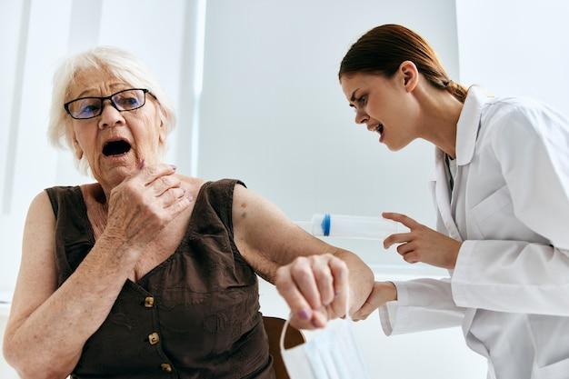 Een oudere vrouw op een doktersafspraak in een groot spuitziekenhuis