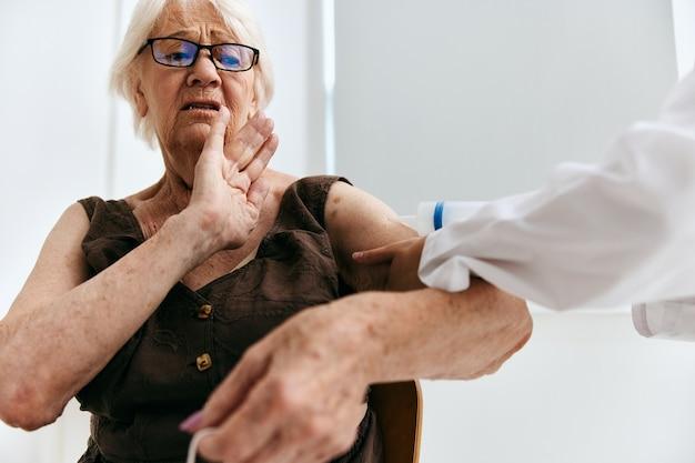 Een oudere vrouw op een doktersafspraak spuit injectie vaccin paspoort