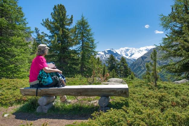 Een oudere vrouw rust tijdens een trektocht door de alpen