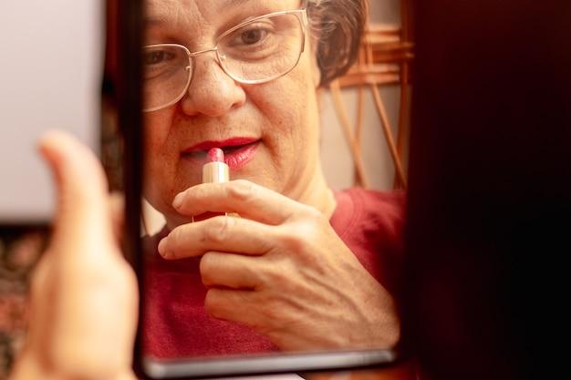 Een oudere vrouw schildert haar lippen met lippenstift en zorgt voor haar schoonheid. ernstige oudere vrouw brengt lippenstift aan voor een spiegel. weerspiegeling van een vrouw in de spiegel