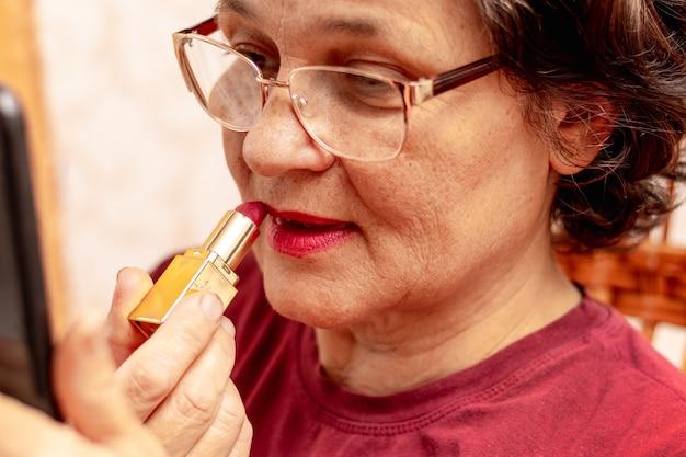 Een oudere vrouw schildert haar lippen met lippenstift en zorgt voor haar schoonheid. ernstige oudere vrouw brengt lippenstift aan voor een spiegel
