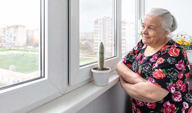 Een oudere vrouw staat bij het raam en kijkt in de verte.