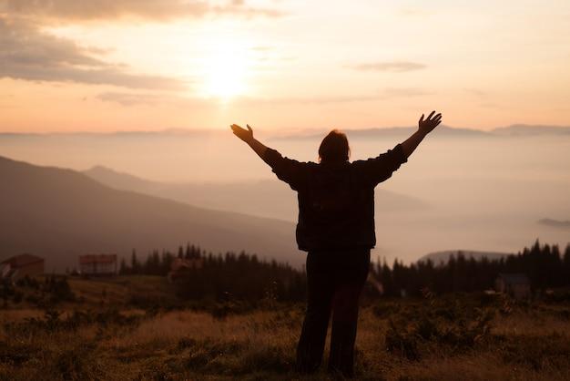 Een oudere vrouw staat op volle hoogte en bidt in de bergen, strekt haar armen uit naar de hemel.