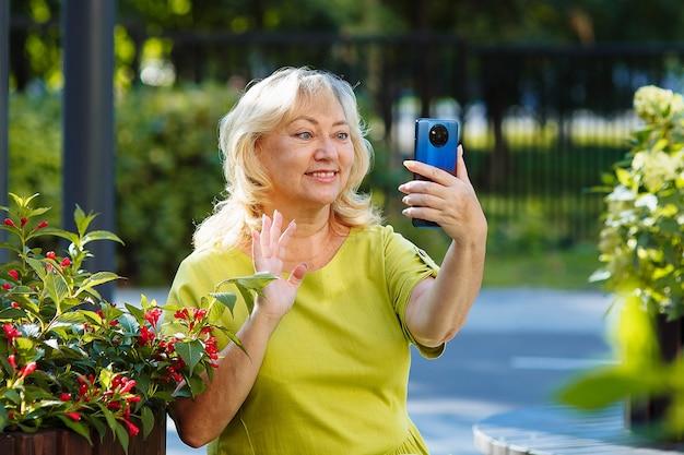 Een oudere vrouw telefoneert via videolink