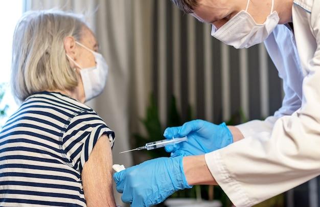 Een oudere vrouw wordt in een verpleeghuis ingeënt tegen covid-19.