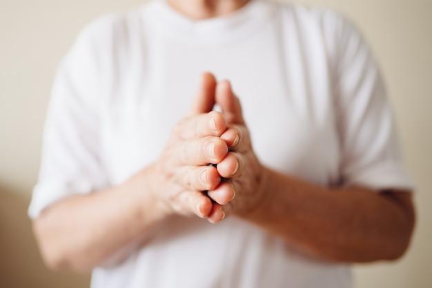 Een oudere vrouw wrijft twee handen tegen elkaar. wrijf handcrème concept.