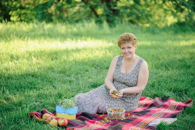 Een oudere vrouw zit op een plaid en heeft kleurrijke pasta in haar handen.