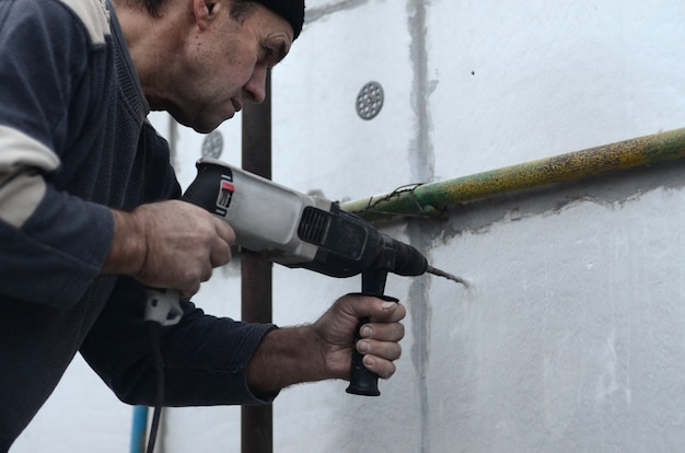 Een oudere werkman boort een gat in een muur van piepschuim