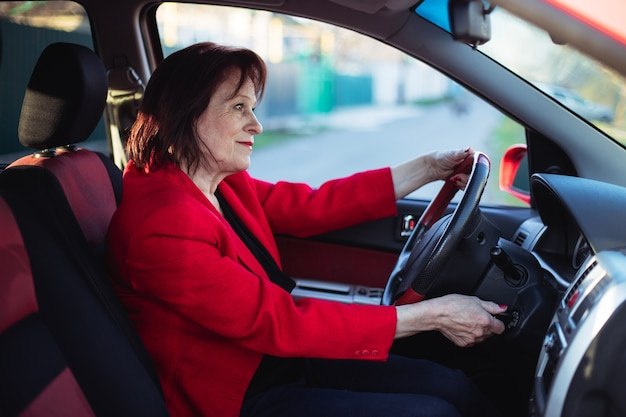 Een oudere zakenvrouw rijdt in haar auto. gluurt uit op de hoofdweg