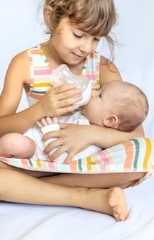 Een oudere zus voedt een pasgeboren baby