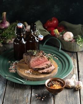 Een ovengebakken stuk rosbief en twee flessen donker bier op een groen, ijzeren dienblad in landelijke stijl