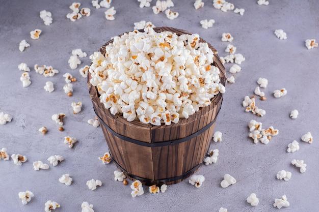 Een overdreven gevulde houten emmer in het midden van verspreide popcorn op marmeren achtergrond. hoge kwaliteit foto