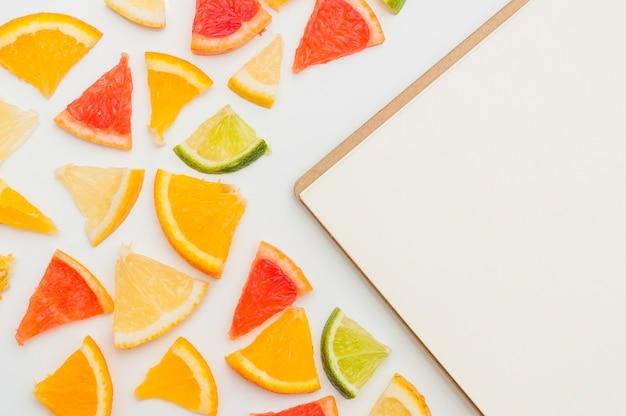 Een overheadkosten van driehoekige citrusvruchtenplakken dichtbij de lege blocnote op witte achtergrond