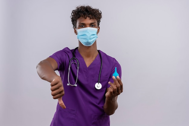 Een overstuur jonge knappe donkere arts met krullend haar in violet uniform met een stethoscoop gezichtsmasker met duimen naar beneden terwijl hij een klysma vasthoudt