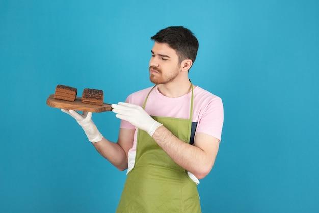 Een overstuur man met verse plakjes cake op blauw.