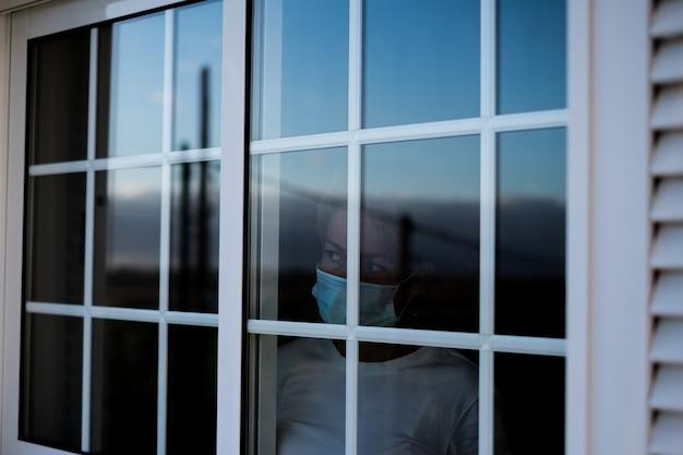 Een overstuur, verdrietige en bezorgde vrouw in een ziekenhuis of thuis die van binnen naar buiten kijkt, dacht aan het raam - jonge volwassene met een masker in lockdown en quarantainetijd