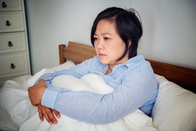 Een overstuur vrouw peinzend in bed