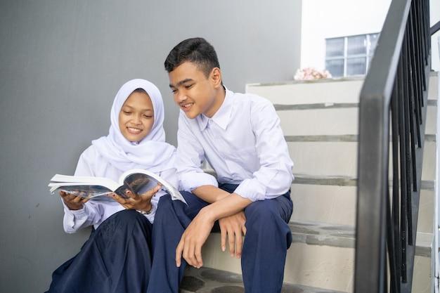 Een paar aziatische tieners in middelbare schooluniformen studeren samen met behulp van een boek