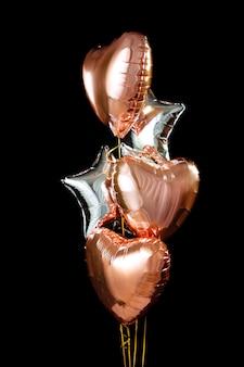 Een paar ballen folie gevuld met helium hart bal object voor verjaardag, valentijnsdag. geïsoleerd op zwarte achtergrond.