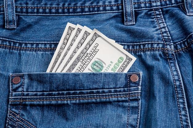 Een paar biljetten van honderd dollar steken uit de achterzak van een spijkerbroek.