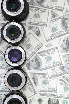 Een paar fotografische lenzen ligt op de achtergrond van heel wat dollarrekeningen. ruimte voor tekst