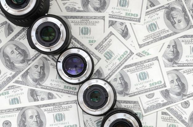Een paar fotografische lenzen ligt op de achtergrond van heel wat dollarrekeningen.