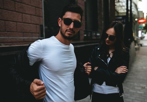 Een paar gekleed in zwart en wit met een zonnebril op hun ogen in de stad. straat liefdesverhaal