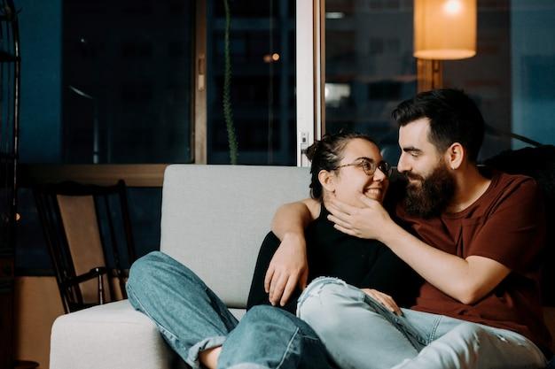 Een paar geliefden kijken elkaar liefdevol op de bank terwijl ze gezichten aanraken met kopie ruimte
