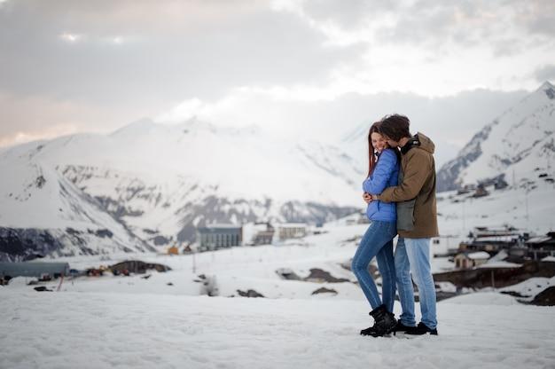 Een paar geliefden, knuffelen elkaar op het toneel van sneeuwbergen en lachen