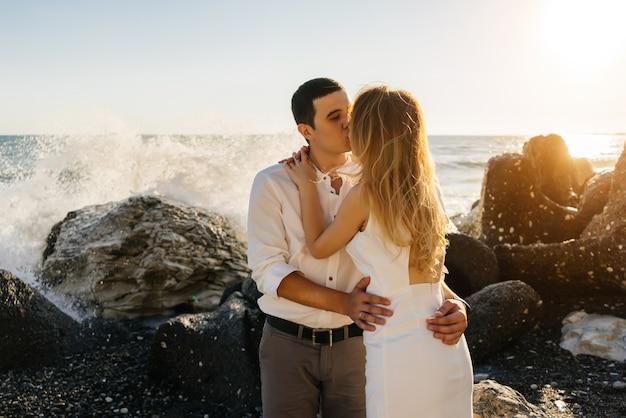 Een paar geliefden kussen naast de zee, op een steenachtige kust, grote golven, een zonnige dag