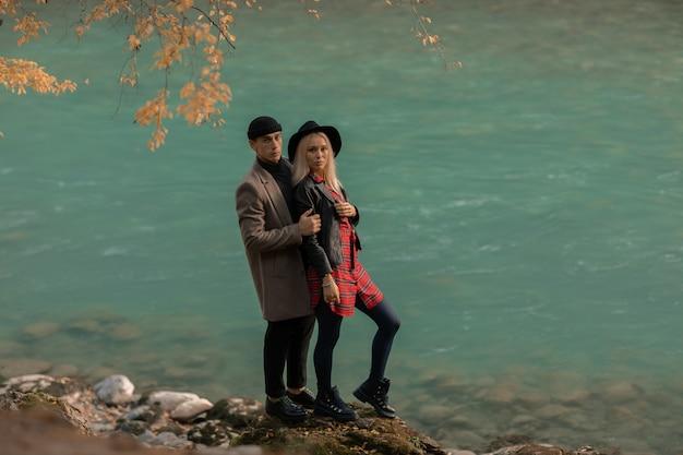 Een paar geliefden man en vrouw staan bij het meer tussen de bergen.