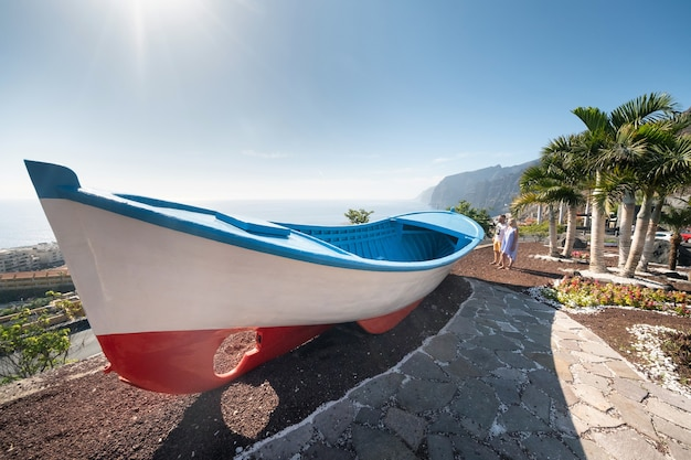 Een paar geliefden op een enorme boot, vlakbij het strand bij de kliffen van acantilados de los gigantes, tenerife, spanje.
