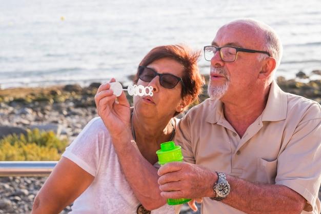 Een paar getrouwde senioren zitten op het strand en blazen een zeepbel met de zee op de achtergrond - samen plezier maken