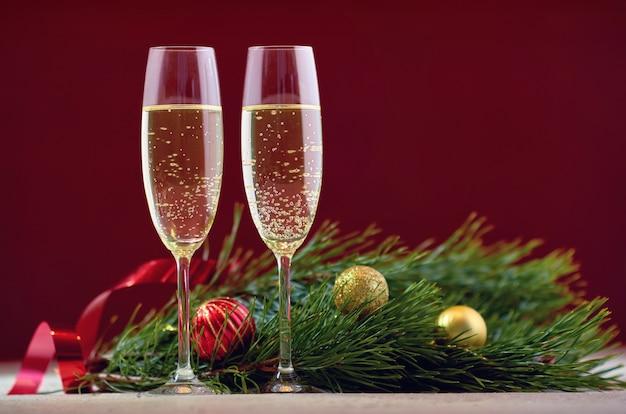 Een paar glazen champagne op een houten tafel met gouden kerstballen, een rood lint met een takje sparren