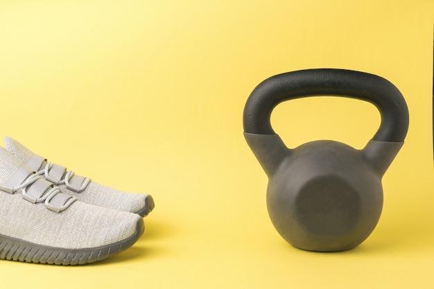 Een paar grijze sneakers en een kettlebell op een gele achtergrond. sportieve levensstijl.