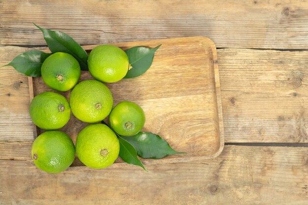 Een paar groene limoenen op een dienblad op een houten achtergrond bovenaanzicht