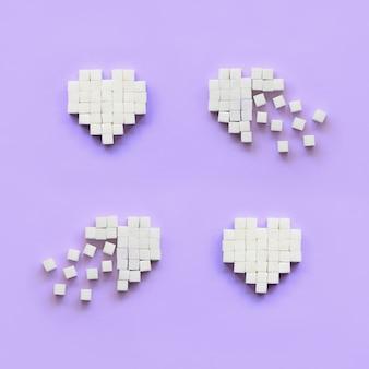 Een paar harten gemaakt van suikerklontjes ligt op een trendy pastel violet