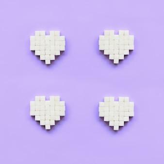 Een paar harten gemaakt van suikerklontjes ligt op een trendy pastel violette achtergrond