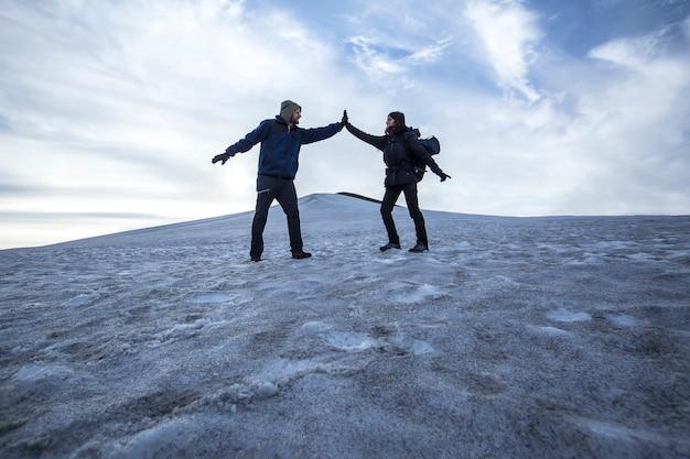 Een paar in de sneeuw op de landmannalaugar-trektocht, ijsland
