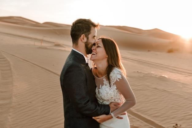 Een paar in hun trouwjurken in de woestijn