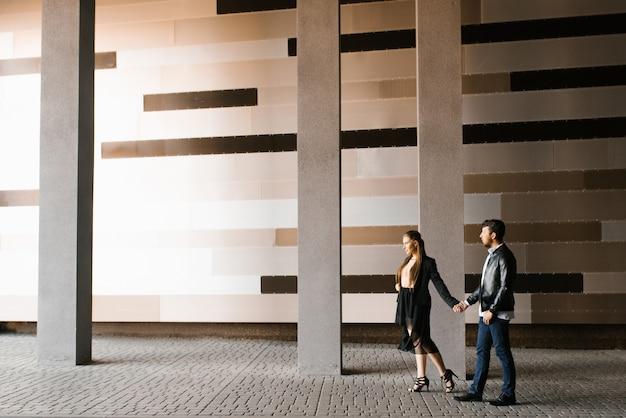 Een paar in zwarte kleding loopt langs de stadsmuur.