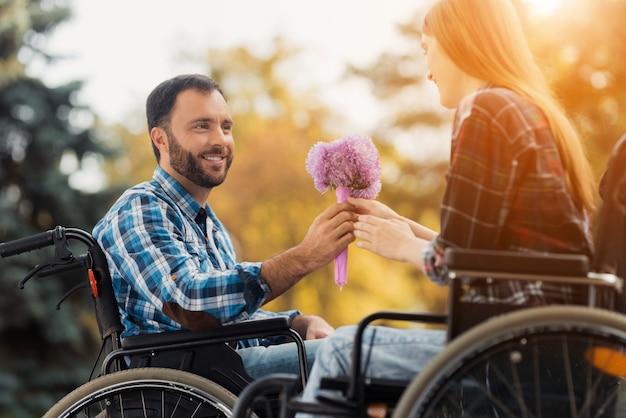 Een paar invaliden op rolstoelen ontmoetten elkaar in het park