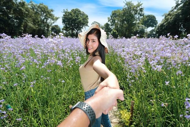 Een paar jonge aziatische reiziger hand in hand onder naga bloem crested veld in de natuur op vakantie en met een gelukkige tijd