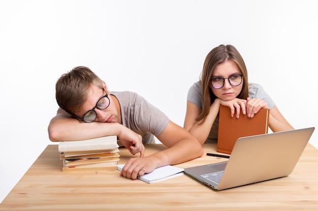 Een paar jonge mensen met een bril zien eruit alsof ze het zat zijn om huiswerk te leren